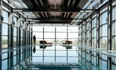 Szklana bryła basenu na ostatnim piętrze hotelu Andels z widokiem na rynek odrestaurowanej Manufakt
