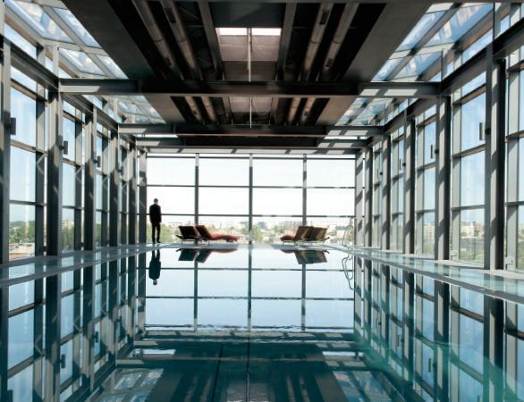 Szklana bryła basenu na ostatnim piętrze hotelu Andel's z widokiem na rynek odrestaurowanej Manufakt