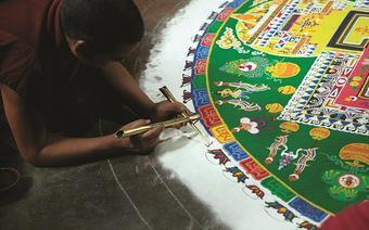 Przygotowanie mandali – mnich sypie piasek o różnych kolorach, ziarnko po ziarnku