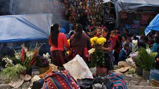 Przed kościołem kobiety ubrane w tradycyjne, kolorowe stroje sprzedają kwiaty.