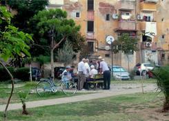 Między blokami w Tiranie starsi panowie grają w domino.