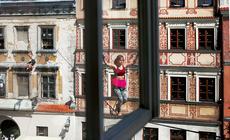 Slacklinerka spaceruje pośród kamienic na rynku w Lublinie