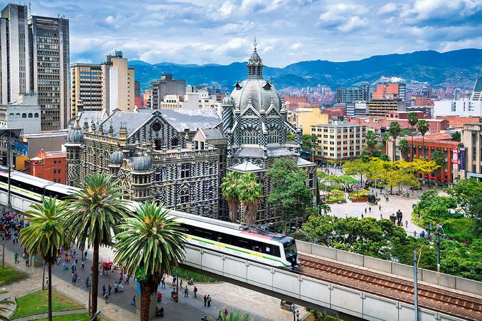 Wcentrum Medellin stare łączysię znowym. Pociąg metra przejeżdża tuż obok Pałacu Kultury im.Rafaela Uribe Uribe
